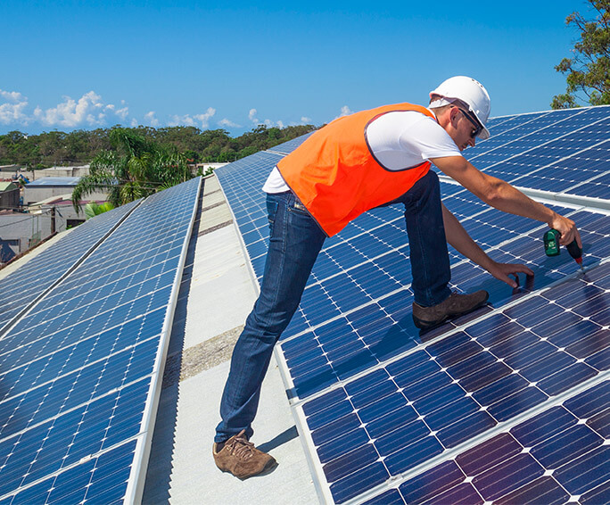 Contractor installing solar panels on the roof of a commercial building