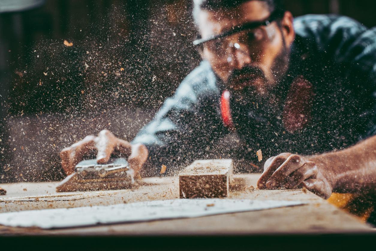A young carpenter cutting wood