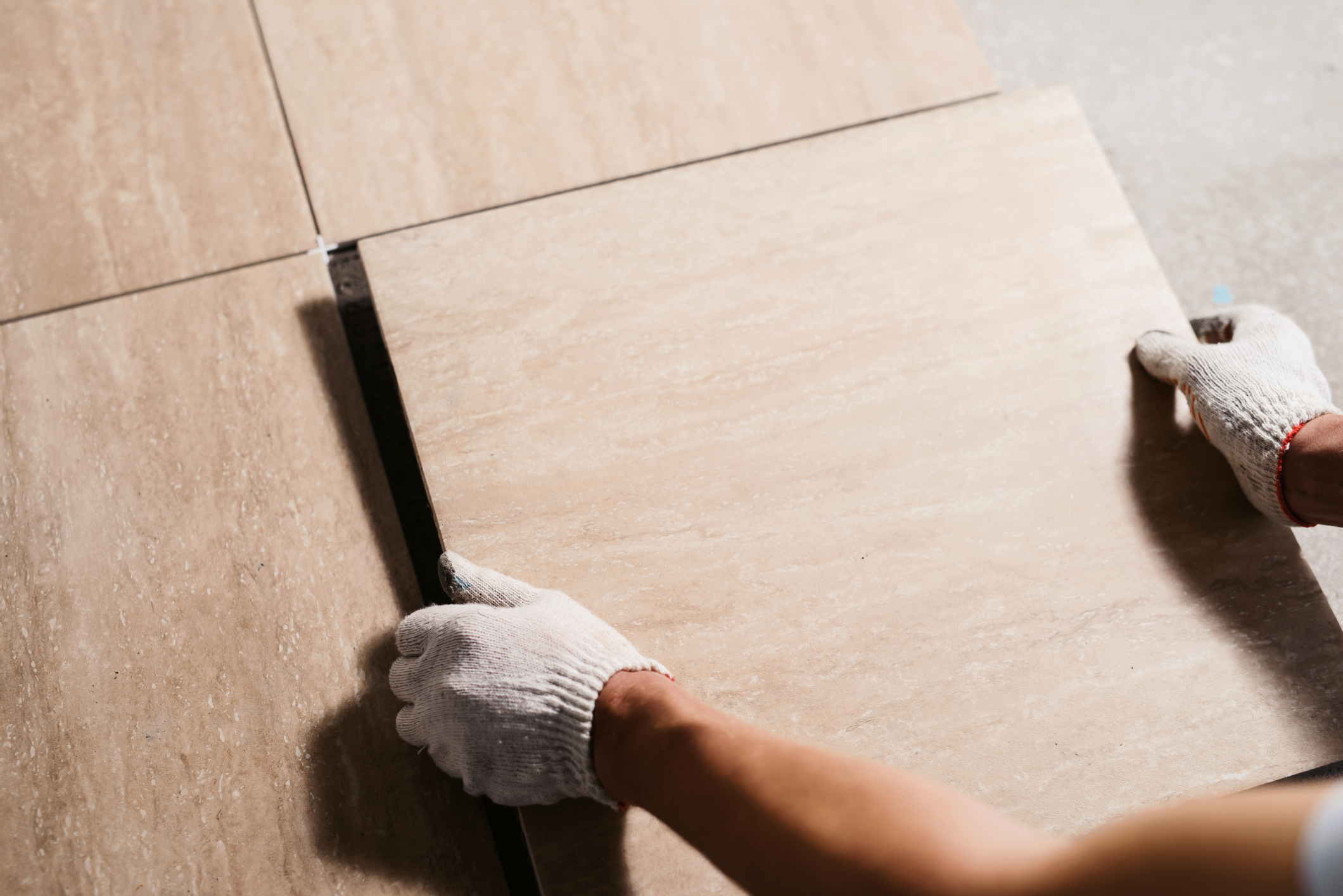 A Los Angeles contractor's hands laying down ceramic tile.