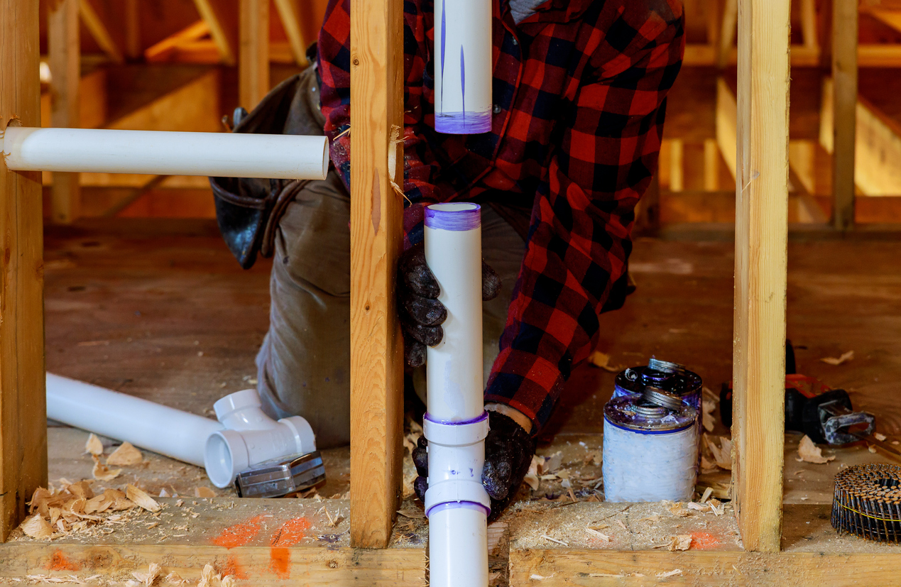 Plumber installing primer and glue PVC pipe at construction home