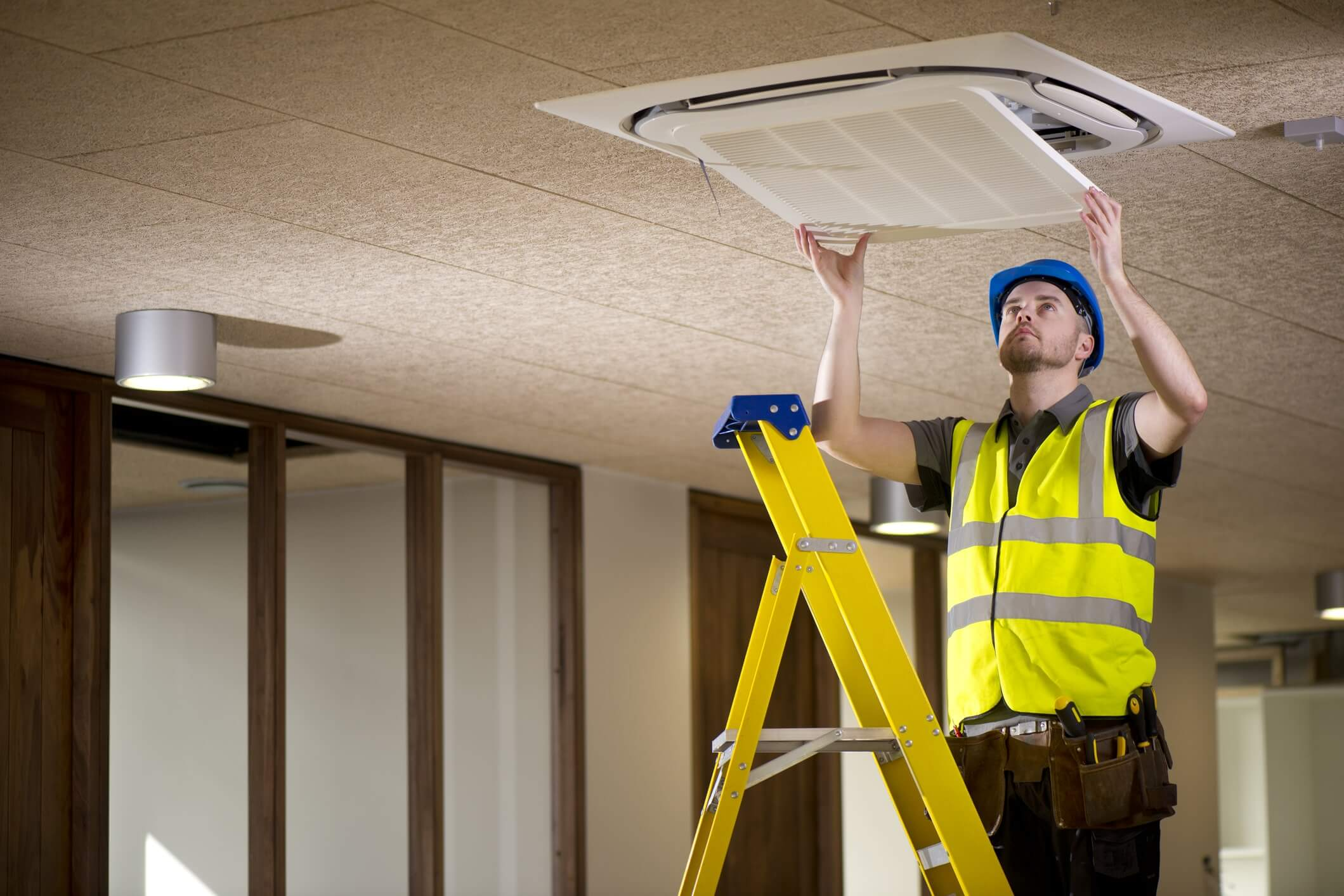 An HVAC technician standing on a ladder and removing a vent cover
