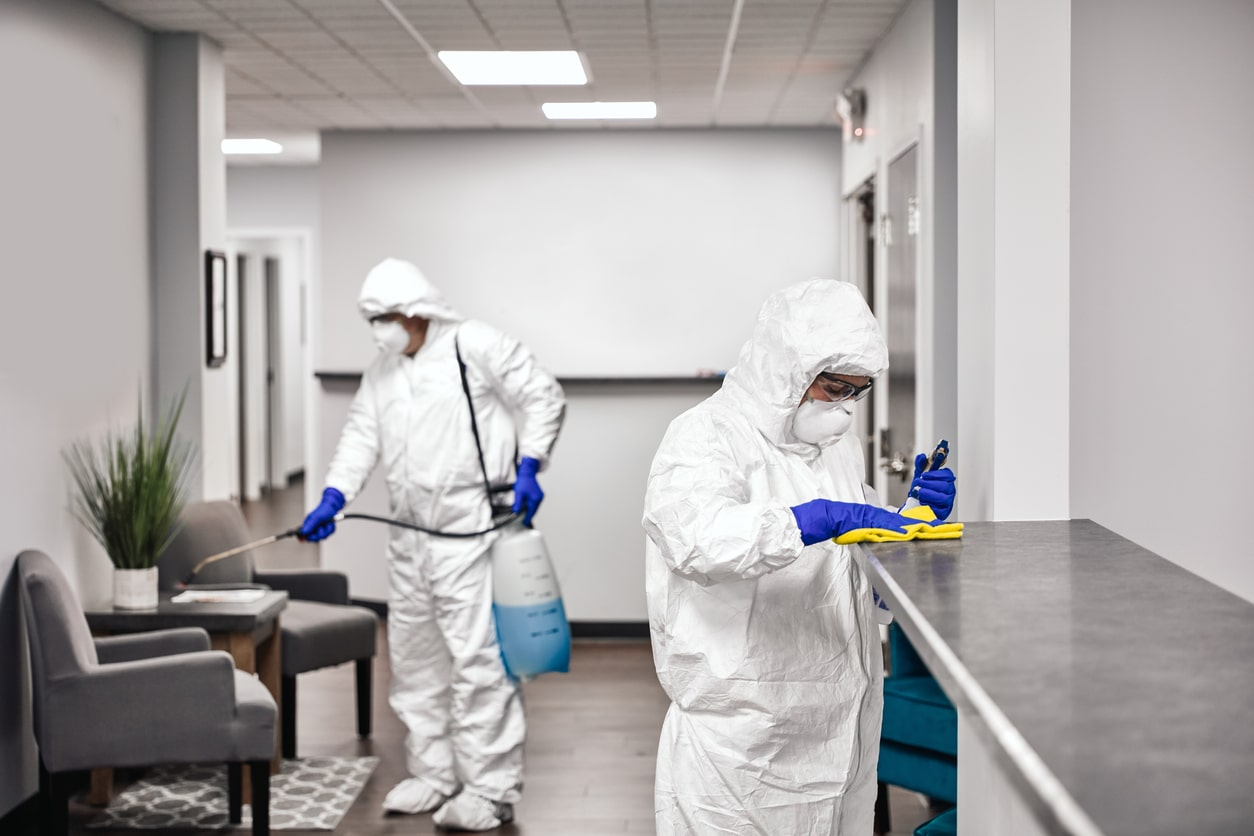 Two employees in hazmat suits disinfecting all surfaces in an office