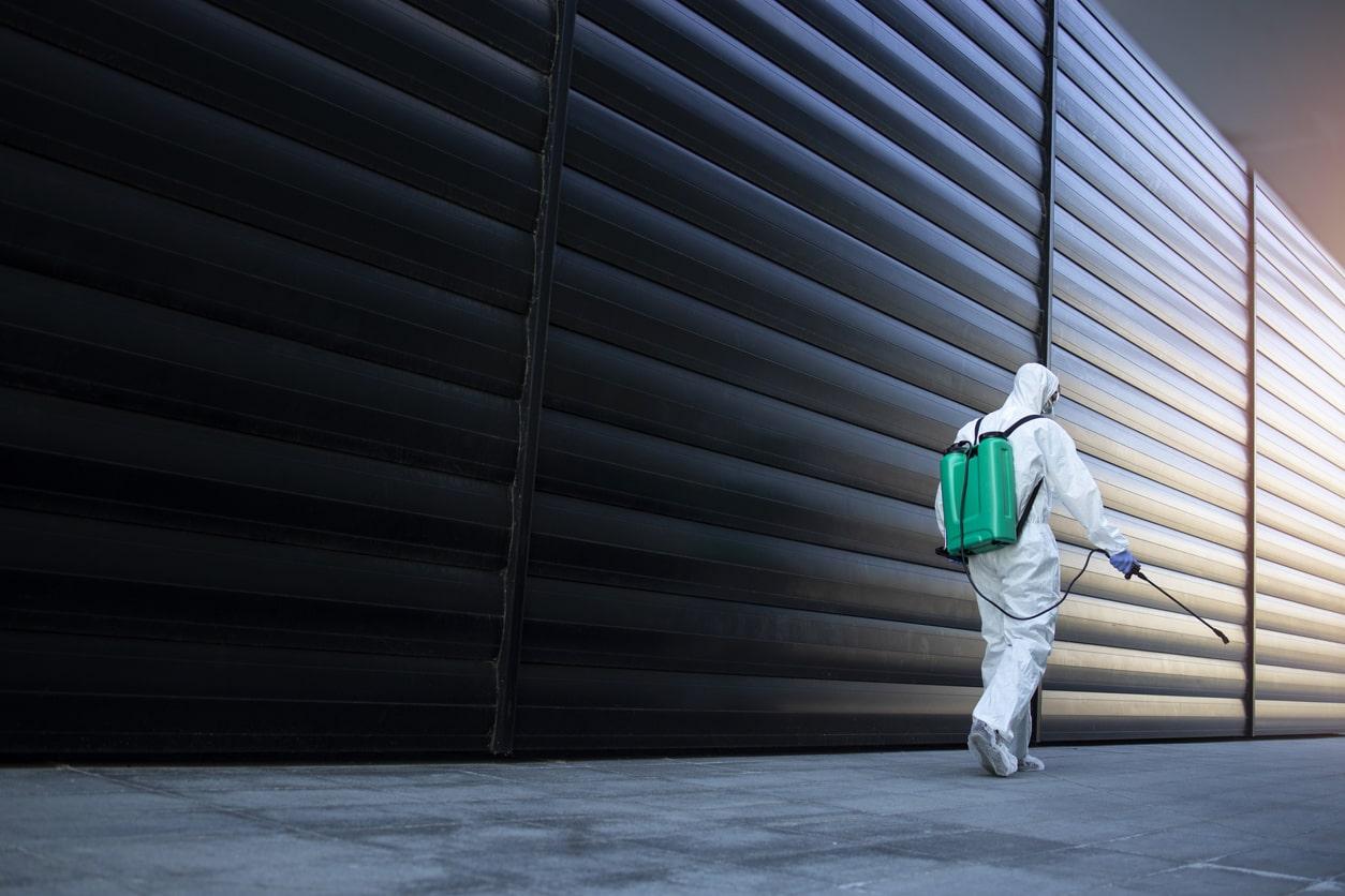 A Los Angeles sanitation worker walking beside a wall