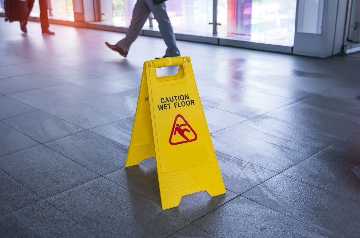 A 'caution wet floor' sign on a wet floor with people walking in the background