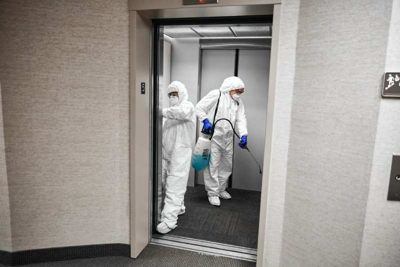 Two employees in hazmat suits disinfecting an elevator