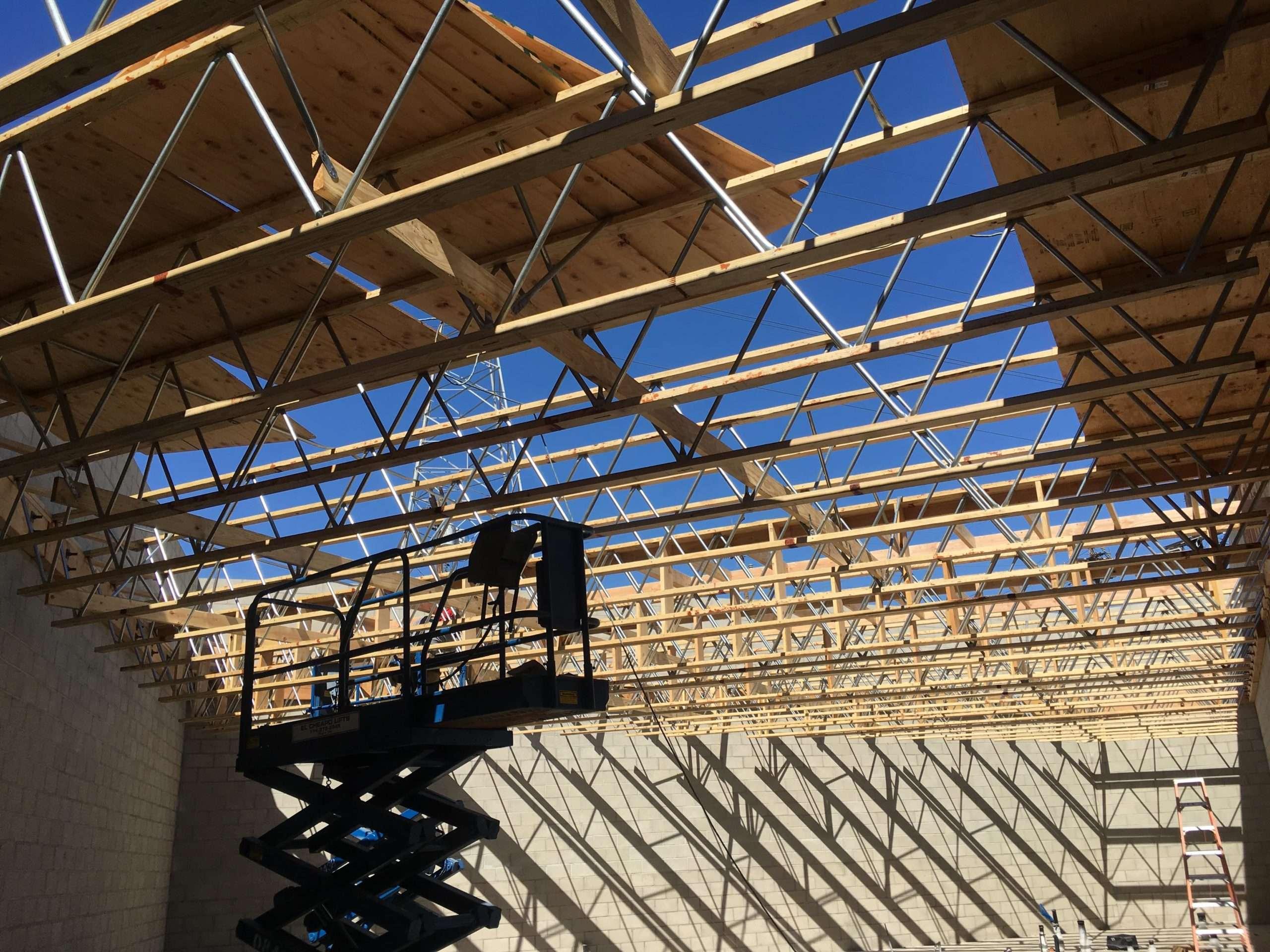 An empty scissor lift under a roof in progress
