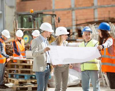 Two male and two female construction workers discussing a blueprint