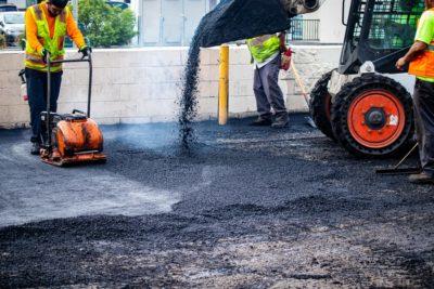 Three contractors pouring asphalt onto D&D plaza's old parking lot