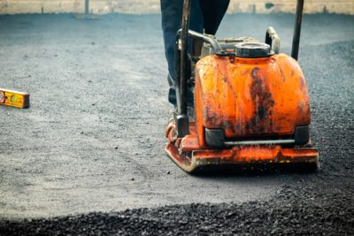 Contractor compacting a freshly laid asphalt parking lot with a plate compactor