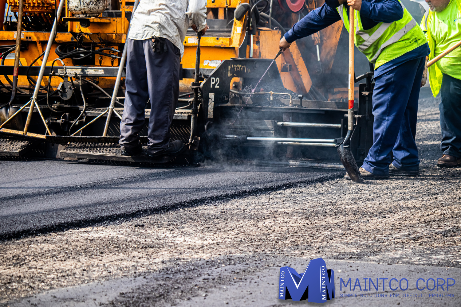 Three Maintco employees in the process of paving a business's parking lot