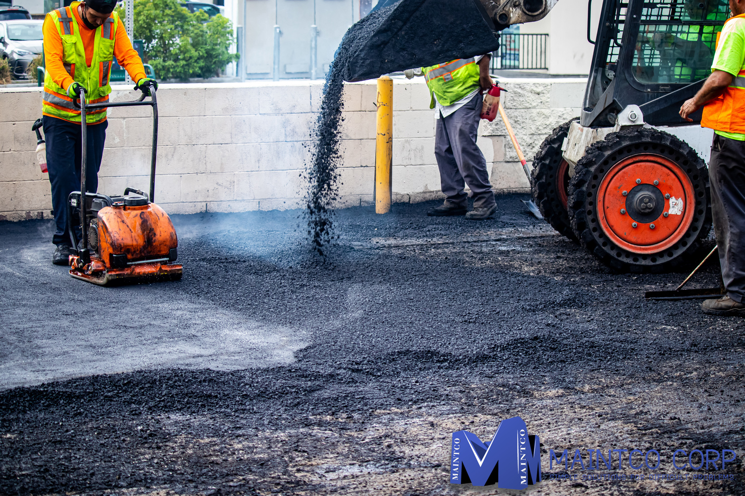 Maintco employees pouring asphalt to pave a parking lot