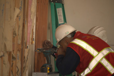Maintco Corp employee insulating a wall at Carbon Health