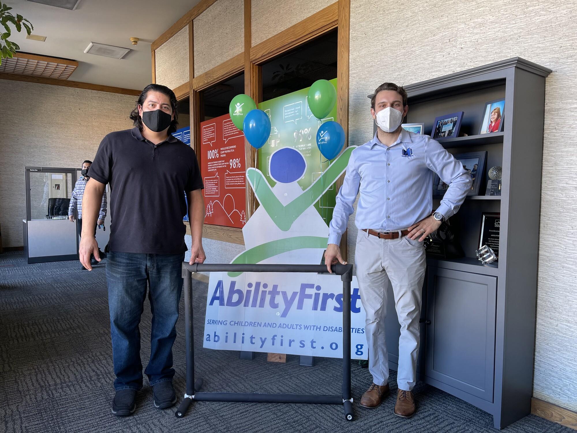 Maintco Corp's Alan Radojcic and AbilityFirst's Oscar Franco smiling next to sneeze guard for photo