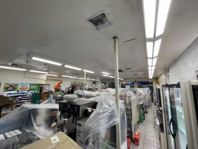 The interior of a 7-Eleven under renovation with plastic wrap covering appliances