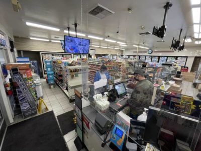 A cashier helping a customer check out in a renovated 7-Eleven