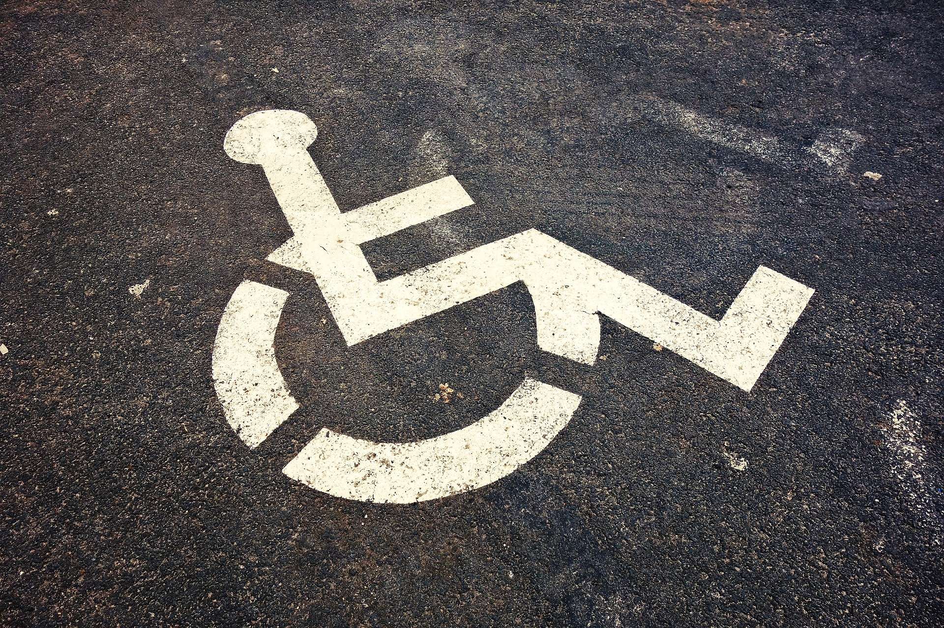 Close up of the International Symbol of Access painted in white on asphalt