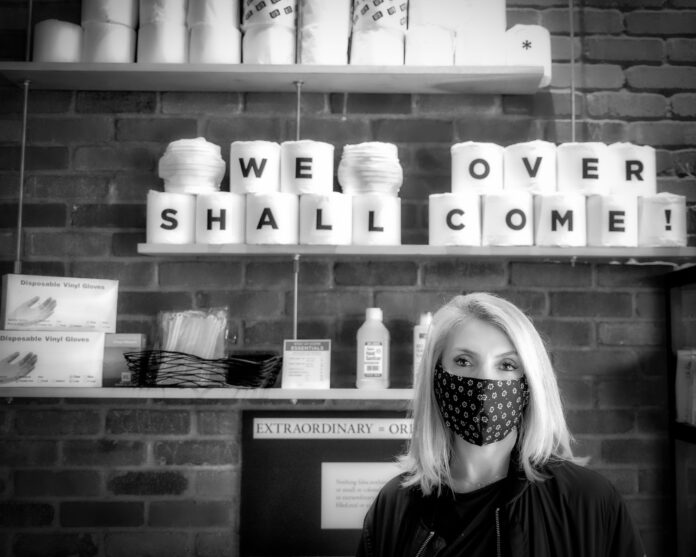 Inna Tuler wearing a mask while standing in front of a 'We Shall Over Come' message